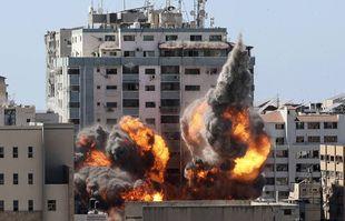 Une explosion près d'un immeuble abritant divers médias internationaux, dont l'Associated Press, après une frappe aérienne israélienne le samedi 15 mai 2021 dans la ville de Gaza.