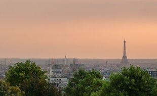 Le 23 juillet 2018, à Paris. Vue panoramique depuis le belvédère de Belleville lors d'un pic de pollution, à 21 heures juste après le coucher du soleil. A droite, la tour Eiffel; plus à gauche, on distingue le dôme des Invalides.