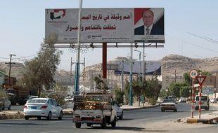 Sanaa (Yémen), le 22 février 2015. Des yéménites entrent dans la capitale en passant devant une affiche du président Abedrabbo Mansour Hadi.