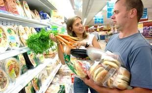 Un couple au supermarché: les hommes consomment plus de produits transformés que les femmes.