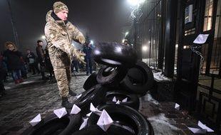 Un manifestant ukrainien jette un pneu devant l'ambassade russe à Kiev, après l'incident dans le détroit de Kertch, le 25 novembre 2018.