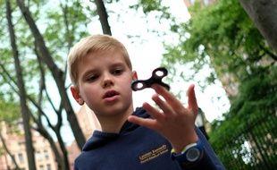 Un enfant joue avec une toupie «Hand Spinner» dans un parc de New-York.