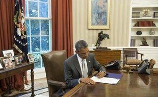 Le président américain Barack Obama signe un document prévoyant l'octroi de 225 millions de dollars supplémentaires à Israël pour le financement du Dôme de fer, le 4 août 2014 à la Maison Blanche