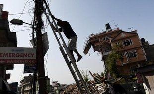 Un Népalais essaie le 1er mai 2015 de reconnecter des câbles au réseau électrique de Katmandou, gravement endommagé par le séisme du 25 avril