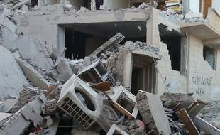 """People walk past a building that was reportedly targeted by the US-led coalition,  in the Islamic State (IS) controlled Syrian city of Raqqa on November 11, 2014. The leader of the moderate Syrian opposition accused the US-led coalition in an interview of having a """"confused"""" strategy in Iraq and Syria that targeted jihadists but turned """"a blind eye"""" to crimes by Syrian President Bashar al-Assad.  AFP PHOTO/RMC/STR"""