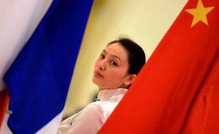Une femme se tient entre un drapeau français et un drapeau chinois lors d'une cérémonie pour le 50e anniversaire des relations diplomatiques franco-chinoises, à Pékin le 27 janvier 2014.