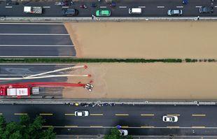 Photo aérienne prise le 22 juillet 2021 montrant des pompiers pompant l'eau de pluie d'un tunnel routier à Zhengzhou, capitale de la province du Henan (centre de la Chine).