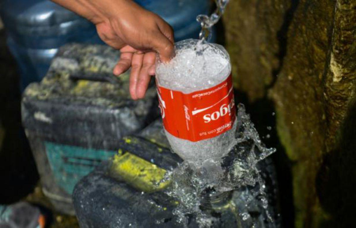 Un homme remplit un bidon avec de l'eau de la montagne Guaraira Repano à Caracas, le 21 Janvier 2016 – FEDERICO PARRA AFP