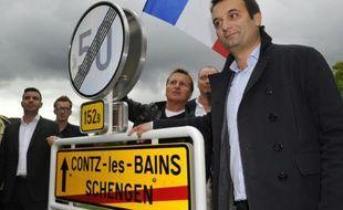 Florian Philippot vice-président du FN pose devant le panneau de la ville de Schengen (Luxembourg), le 19 septembre 2015 où il a symboliquement célébré la mort annoncée des accords de Schengen