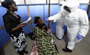 Des personnels de santé d'un centre de l'Organisation mondiale de la Santé à Monrovia auscultent une malade d'Ebola, le 3 octobre 2014