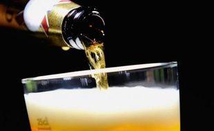 Une personne sert un verre de bière.