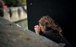 Une personne en prière près de Notre-Dame de Paris, le 16 avril 2019, au lendemain de l'incendie de la cathédrale. Illustration.