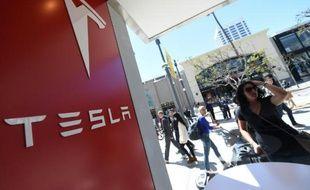 """Le 31 mars 2016 une femme regarde la vitrine d'une boutique Tesla à Santa Monica (Californie) aux États-Unis où les américains ont le privilège de réserver, sans même l'avoir vue, la """"Model 3"""" contre 1.000 dollars."""