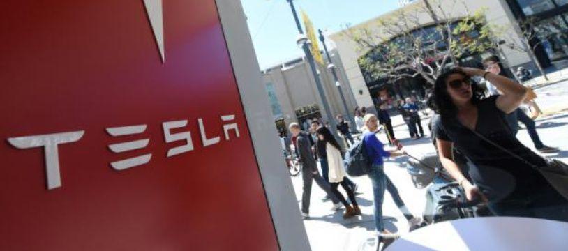 """Le 31 mars 2016 une femme regarde la vitrine d'une boutique Tesla à Santa Monica (Californie) aux États-Unis où les américains ont le privilège de réserver, sans même l'avoir vue, la """"Model 3"""" contre 1.000 dollars"""