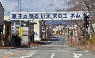 Photo prise le 10 mars 2014, montrant une pancarte claironnant: «L'énergie nucléaire, l'énergie d'un avenir radieux», à Futaba, près de Fukushima, au Japon.