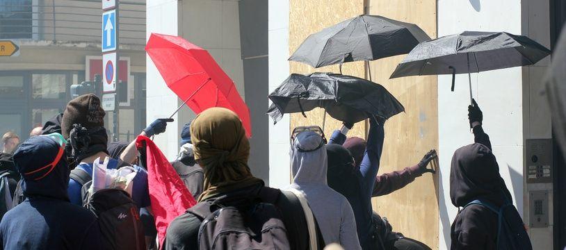 Cachés sous des parapluies, des manifestants ont pris pour cible des façades de banques lors de la manifestation du 19 avril 2018 à Rennes.
