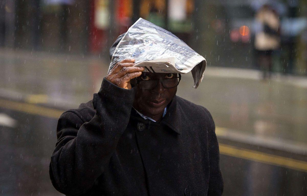 Un homme se protège de la pluie - Illustration – Dominic Lipinski/AP/SIPA