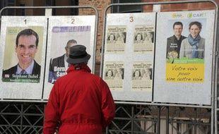 Une personne regarde des affiches électorales sur des panneaux, le 16 mars 2011 à Rodez, en vue des élections cantonales.