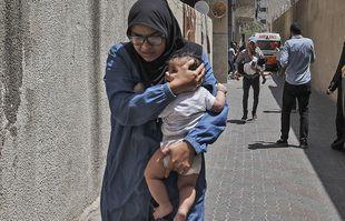 Des Palestiniens évacuent un bâtiment visé par les bombardements israéliens dans la ville de Gaza le 11mai 2021.