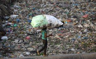 Un homme portant sur son dos un sac de déchets plastique, le 30 mai 2018, dans un bidonville de New Delhi (Inde).