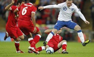 Wayne Rooney se faisant tacler par un défenseur gallois lors d'un match Angleterre-Pays de Galles disputé le 6 septembre 2011 à Londres.