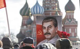 Les partisans du parti communiste tiennent un portrait de Staline sur la Place Rouge à Moscou, le 5 mars 2021.