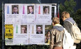 Deux jeunes observant les portraits des candidats à la Présidentielle de 2012 accompagnés d'un message de sensibilisation aux risques du VIH