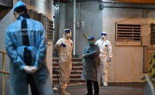 Du personnel médical attend près de l'entrée d'un lotissement résidentiel, à Hong Kong, le 11 février 2020, après que deux personnes dans le bloc ont contracté le coronavirus.
