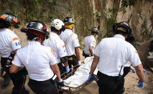 Des pompiers transportent un corps retrouvé dans les ruines du village d'El Cambray II, dans la municipalité de Santa Catarina Pinula, à 15 km à l'Est de Guatemala City, le 4 octobre 2015