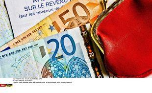 Porte-monnaie avec des billets en euros et avis d'impôt sur le revenu
