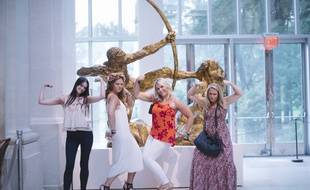 """Des participantes au """"Badass bitches tour"""" posent au Metropolitan Museum of Art de New York, devant une sculpture d'Antoine Bourdelle."""