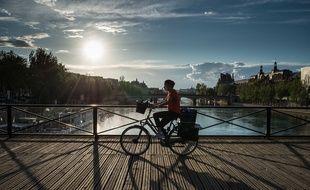Une cycliste masquée sur le Pont des Arts à Paris, le 17 avril 2020.