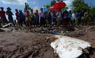 Des villageois laotiens rassemblés près d'un débris de l'avion de Lao Airlines qui s'est abîmé dans le Mékong, le 17 octobre 2013