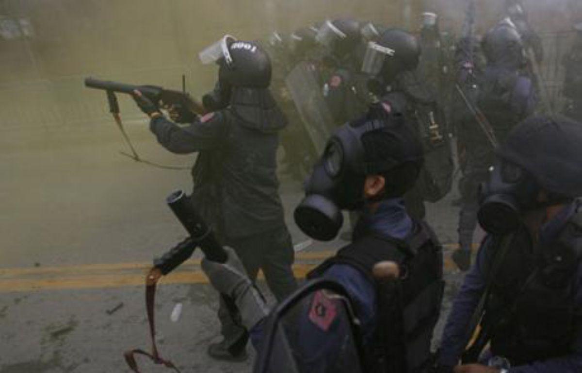 Des policiers dispersent des manifestants au gaz lacrymogènes lors d'une émeute anti-gouvernementale à Bangkok, Thaïlande. – S. SUKPLANG / REUTERS