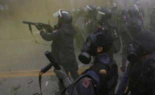 Des policiers dispersent des manifestants au gaz lacrymogènes lors d'une émeute anti-gouvernementale à Bangkok, Thaïlande.