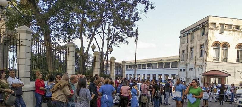 Des travailleurs rassemblés devant le bâtiment Lonja del Comercio (marché du commerce) à La Havane, à Cuba, après le tremblement de terre de magnitude 7,7, vivement ressenti sur l'île et en Jamaïque.