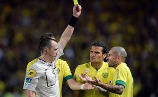 Frenc referee Rudy Buquet (L) gives a yellow card to Nantes' French midfielder Vincent Bessat (R) during the French L1 football match between Nantes and Paris Saint-Germain on May 3, 2015 at the Beaujoire stadium in Nantes, western France. AFP PHOTO / JEAN-SEBASTIEN EVRARD