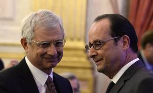 French President Francois Hollande (R) talks with President of the French National Assembly, Claude Bartolone during a symposium on re-founding democracy (Refaire la democratie) on October 6, 2016 at the Hotel de Lassay in Paris. / AFP PHOTO / POOL / STEPHANE DE SAKUTIN
