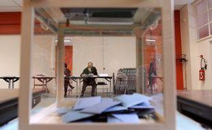 Une personne lit un document en attendant les électeurs le 14 mars 2010 à Melle dans l'un des bureaux de vote installés pour le premier tour des élections régionales.