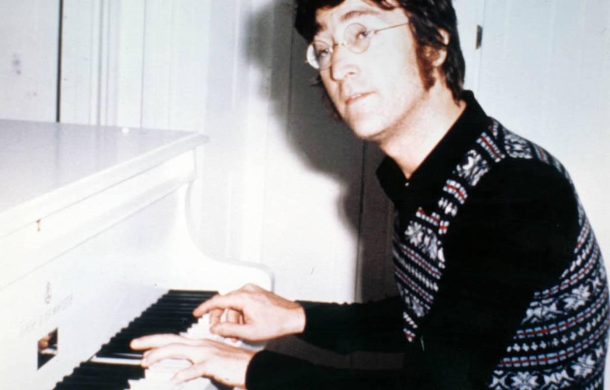 L'artiste John Lennon dans les années 70 avec le piano Imagine – PR