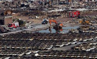 Des véhicules de secours interviennent près de rangées de voitures carbonisées sur le site des explosions de Tianjin, en Chine, le 16 août 2015
