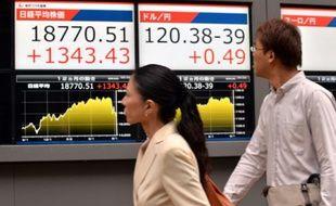 Des passants regardent un tableau d'indices boursiers, le 9 septembre 2015 à Tokyo