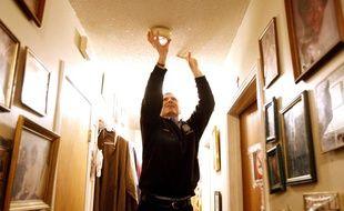 Photo d'illustration d'un homme installant un détecteur de fumée