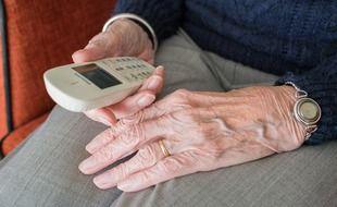 Une personne âgée avec un téléphone à la main (illustration).