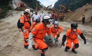 Des équipes de secours transportent le corps d'une victime après un glissement de terrain  à Santa Catarina Pinula, le 6 octobre 2015 au Guatemala
