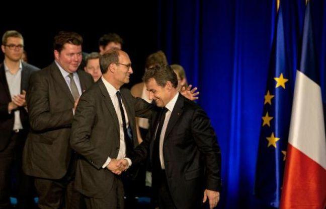 Nicolas Sarkozy (C) salue l'ancien ministre du budget Eric Woerth (G), lors d'un meeting le 9 avril 2015 à Gouvieux dans le nord-est de Paris