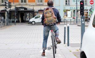 Un cycliste arrêté au feu rouge sur la place de Bretagne, à Rennes.