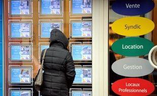 Une femme regarde les annonces dans la vitrine d'une agence immobilière