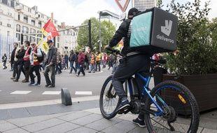 Un livreur Deliveroo patiente à côté du défilé du 1er mai 2018 à Nantes (Illustration).