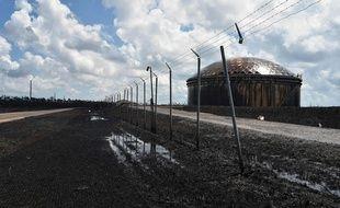 La marée noire s'étend sur les champs autour des cuves de pétrole.